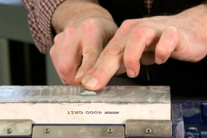 Remove the wire edge by holding the back of the chisel flat on the stone.